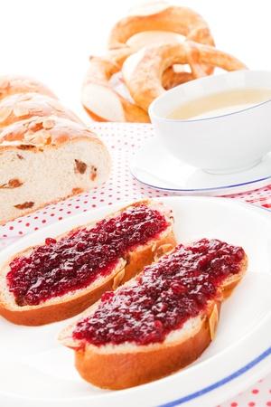 fruitcake: Sweet european breakfast. Traditional fruitcake with marmalade, tea in background.