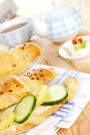 Luxurious delicious breakfast background. Croissatn with fresh vegetable, tea and financial times in background. Good morning concept. photo