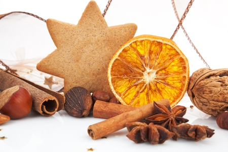 Traditional classic natural christmas decoration. Gingerbread, cinnamon, various nuts and orange. Brown festive xmas still life. Stock Photo - 11537140