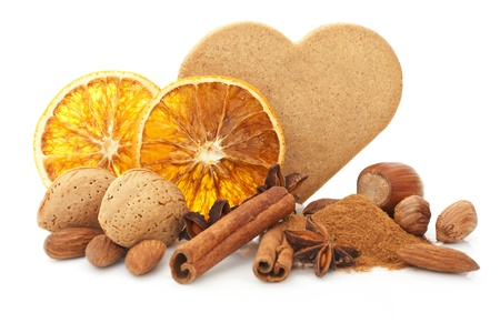 Natural christmas still life with heart shaped gingerbread cookie, orange, various nuts, cinnamon, anise and spices. Brown and orange natural xmas. photo