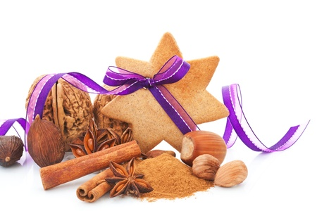 Gingerbread star cookie with hazelnut, cinnamon and purple ribbon. Natural brown christmas still life. Aromatic culinary spices and various nuts. photo