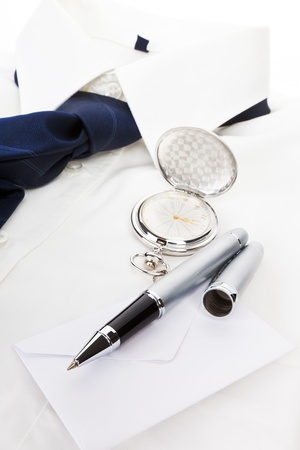 Elegant business still life with white dress shirt, blue tie, pen, envelope and silver pocket watch. Business concept. photo
