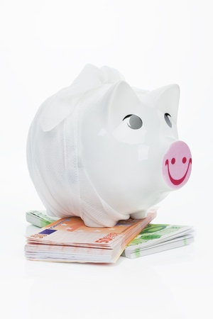 Piggy bank with bandage on fifty and hundred euro notes. Financial crisis concept. photo