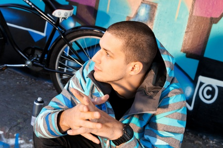 cruiser bike: Young male graffiti artist sitting in front of finished piece on wall with city cruiser bike leaning next to him. Urban culture. Stock Photo