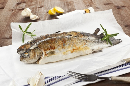 Two grilled trouts with lemon pieces, garlic on white baking paper on kitchen towel on wooden table. photo