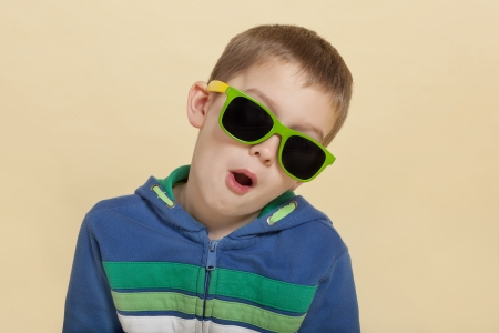 Funky cool young surprised boy with open mouth and yellow and green sunglasses. Youth fashion concept. photo