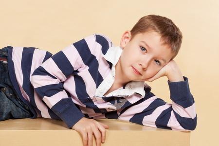 looking into camera: Ragazzo modello giovane sdraiato sul tavolo e guardando in telecamera. Youth concetto di moda.