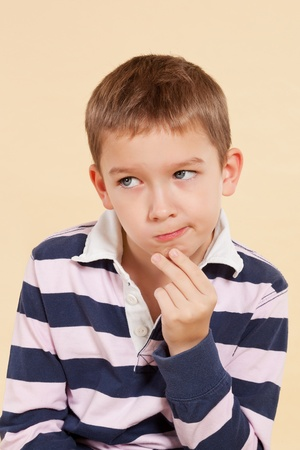 Young white boy isolated on neutral background thinking about a solution of a problem. Facial expressions concept. photo