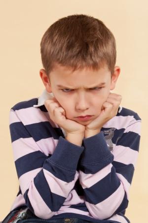 Niño enfadado poco aislado en un fondo neutro. Las expresiones faciales de concepto.