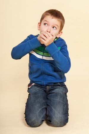 gevangen: Jonge jongen met handen voor zijn mond die op neutrale achtergrond. Gezichtsuitdrukkingen concept. Stockfoto