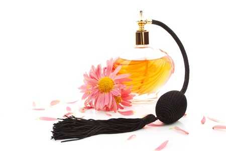 Luxurious perfume bottle atomizer with flower blossom isolated on white background. Feminine beauty concept. photo