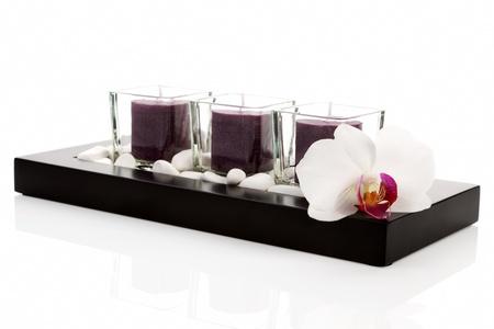 Bienestar, como zen todavía la vida con velas, piedras blancas y flor de la orquídea en la bandeja de negro sobre fondo blanco. Concepto de spa de lujo.