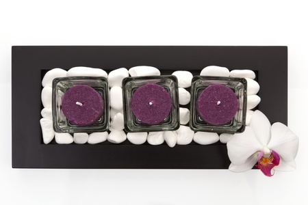 Candles with white stones and orchid blossom zen like spa background. Luxurious minimal wellness concept. photo