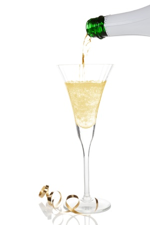 Pouring golden champagne into a glass isolated on white. Luxury celebration concept. photo