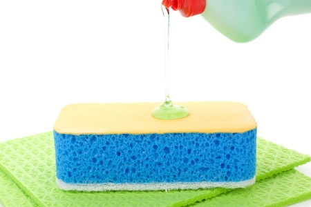 house chores: Liquid cleaner dropping onto cleaning sponge isolated on white background. House chores concept.