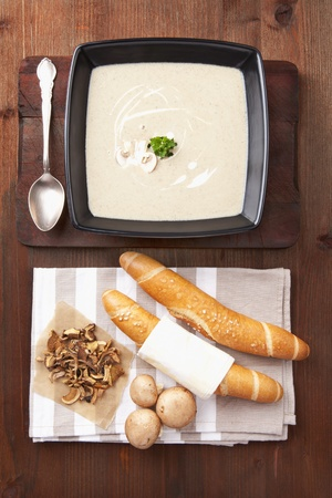 Mushroom cream soup with fresh pastry, fresh and dried mushroom on wooden background. Culinary healthy eating, rustic style. photo