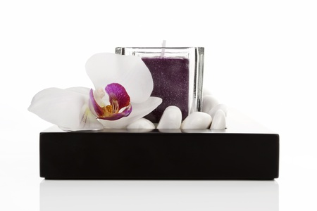 Candles with white stones and orchid blossom zen like spa background  Luxurious minimal wellness concept  photo