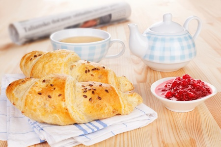 Delicious breakfast. Two croissant, jam, tea and newspaper on wooden background. Sweet french morning concept. photo