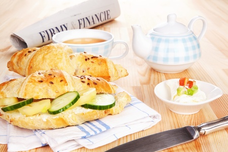 Delicious breakfast. Croissant with cream cheese and fresh vegetables, tea on kitchen cloth on wooden table. Business newspaper in background. photo