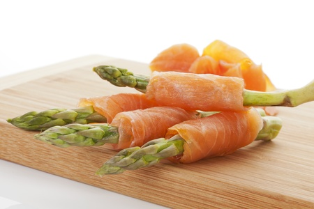 Fresh asparagus and smoked salmon rolls on wooden chopping board isolated on white background. Healthy delicious eating. photo