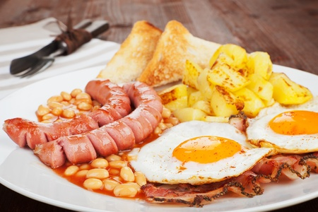 Sausages, beans, beans, ham and egg with toast bread and potatoes  Culinary english eating  photo