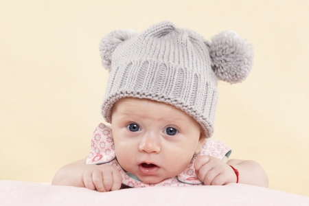 1 2 month: Surprised baby girl with grey hat looking into the camera isolated on neutral background. Cute newborn concept.