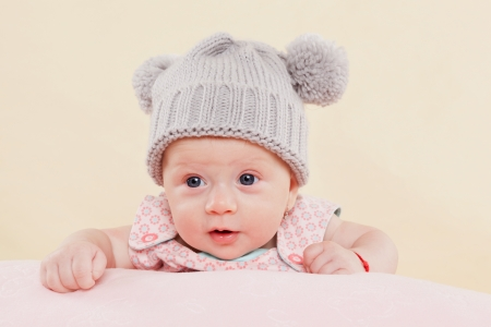 Beautiful cute surprised baby girl with grey cap lying on blanket faced into the camera   Stock Photo - 13708925