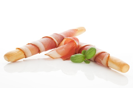 Culinary gourmet starter  Grissini bread wrapped in prosciutto ham  Eating