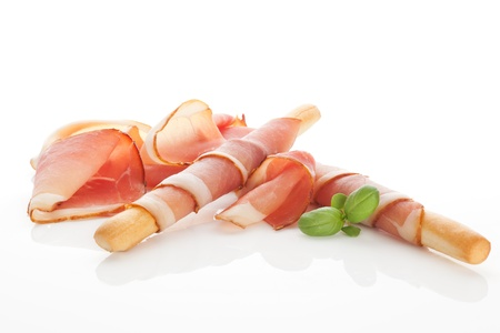 raw ham: Culinary food  Parma ham prosciutto with grissini bread sticks isolated on white background
