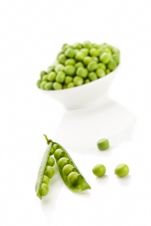 Pea pod and peas in bowl isolated on white background. Culinary summer legume vegetable.  photo
