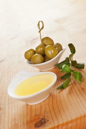 Olive oil and olives in bowls with twig on wooden background  Culinary traditional italian cooking Stock Photo - 14320900