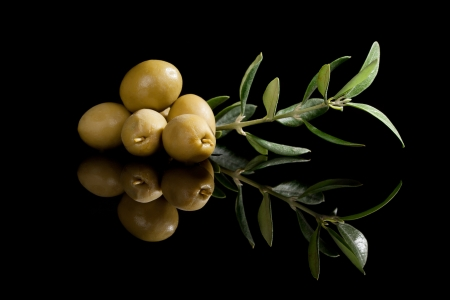 delicious: Green olives with olive branch isolated on black background  Culinary traditional appetizer