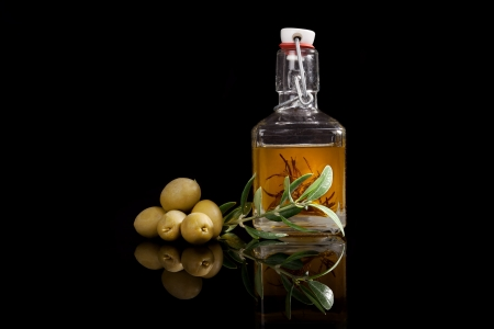 Delicious extra virgin olive oil with fresh olives and olive twig isolated on black background  Traditional culinary condiment  photo