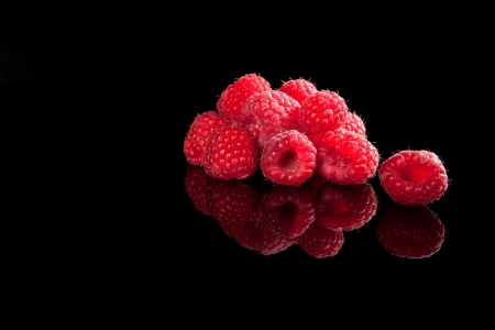 Delicious ripe raspberries isolated on black background with reflection  Luxurious fruit summer background