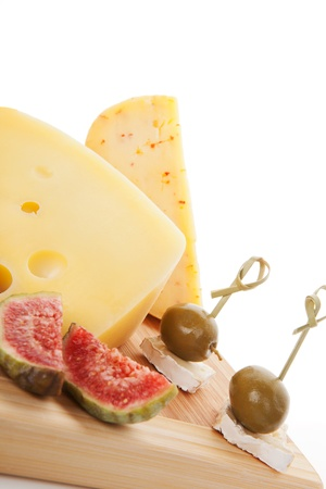 Delicious cheese background with various cheese sorts, fig, green olives on chopping board on white  Culinary appetizer background  photo