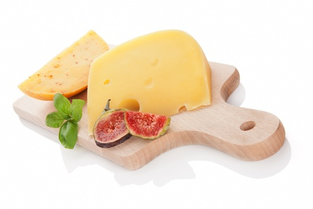 Swiss cheese and gouda piece on wooden cutting board isolated on white background decorated with fig and fresh basil  Luxurious cheese still life  photo