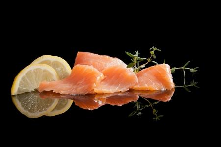 Lyxig skaldjurs bakgrund. Rökt lax med citron och rosmarin isolerade på svart mat. Stockfoto