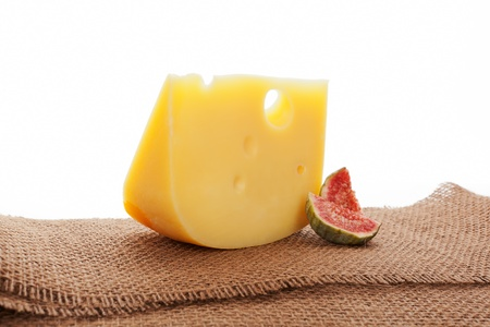 Luxurious swiss cheese emmentaler still life with fig on brown textile, bright country style. Culinary cheese eating. photo