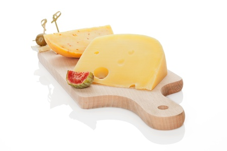 Various cheese pieces on wooden chopping board with fig and olive canape isolated on white. Culinary eating concept. photo