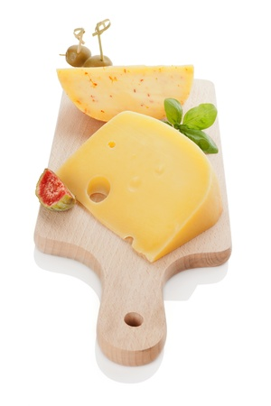 Swiss cheese emmentaler and gouda with olive canape, tropical fruit fig and fresh basil leaves on wooden kitchen board isolated on white. Delicious cheese background. photo