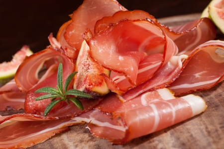Delicious prosciutto slices on wooden chopping board  Culinary traditional ham  photo