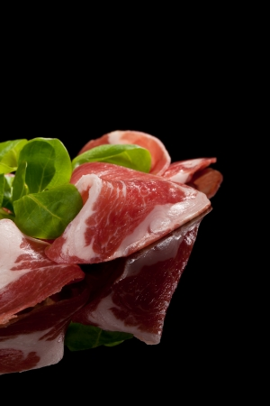 prosciutto: Prosciutto slices with corn salad isolated on black background  Culinary meat eating concept  Country ham  Stock Photo