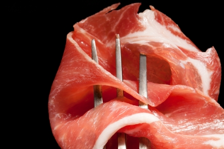 raw ham: Detail of parma ham on antique fork isolated on black background  Culinary meat concept  Prosciutto