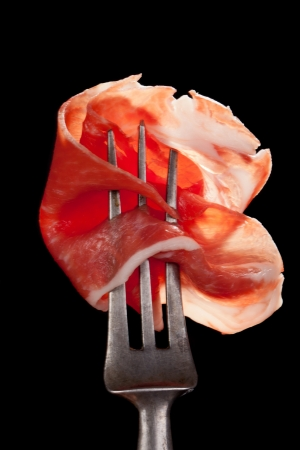 Delicious parma ham on old silver fork detail isolated on black background  Culinary traditional meat eating concept  Stock Photo
