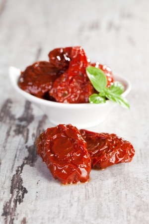 Dried tomatoes pomodoro with fresh basil leaves on white wooden textured background  Culinary traditional mediterranean eating