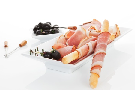 Luxurious modern minimal prosciutto background  Grissino breadsticks wrapped in prosciutto slices with black olives and fresh herbs in white tray isolated on white background  Culinary meat eating  photo
