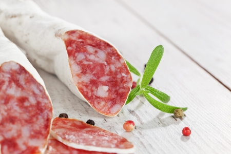 Luxurious traditional spanish sausage fuet on white textured wooden background with fresh herbs and peppercorns  Culinary eating  photo