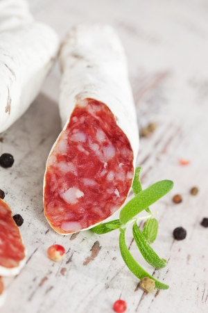 White sausage fuet with fresh herbs and colorful peppercorns on white textured wooden background  Traditional spanish meat  photo
