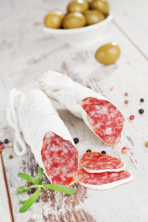 Culinary fuet sausages on white wooden textured background with olives and peppercorns  Gourmet eating  photo