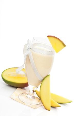 Delicious mango milk shake with fresh mango fruit isolated on white background. Refreshing summer drink. photo